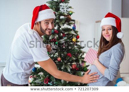 pregnant woman decorating christmas tree Stock photo © dolgachov