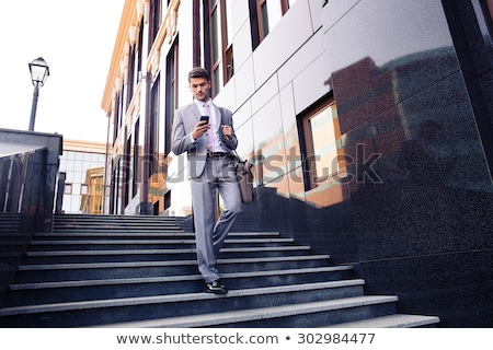 Stock photo: Businessman walking on the stairs and using smartphone outdoors