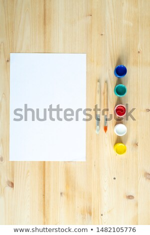 Blank sheet of paper, two paintbrushes and row of colorful paints or gouaches Stock photo © pressmaster