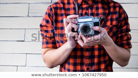 Millennial man mid section with camera against white wood panel Stock photo © wavebreak_media
