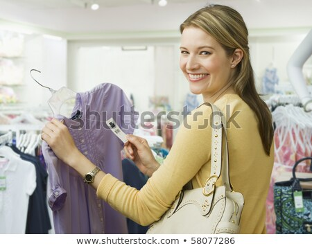 happy woman with sale tags at clothing store stock photo © dolgachov
