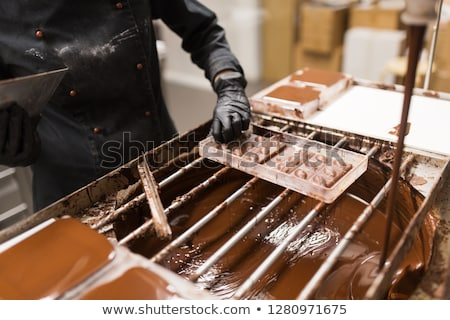 confectioner removing excess chocolate from mold Stock photo © dolgachov