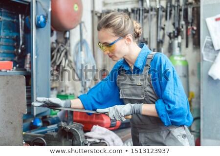 Woman worker in metal workshop deburring workpiece Stock photo © Kzenon