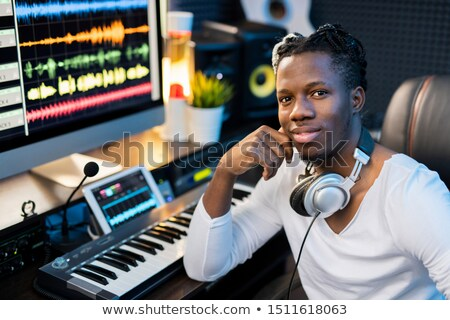 Happy young smiling mixed-race man with headphones on neck sitting by workplace Stock photo © pressmaster