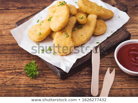 Buttered chicken nuggets on chopping board with wooden forks and ketchup on wooden background. Stock photo © DenisMArt