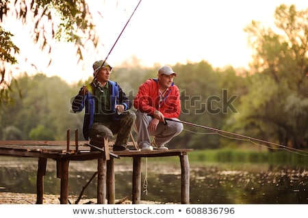 friends with fishing rod, fish and tackle on pier Stock photo © dolgachov