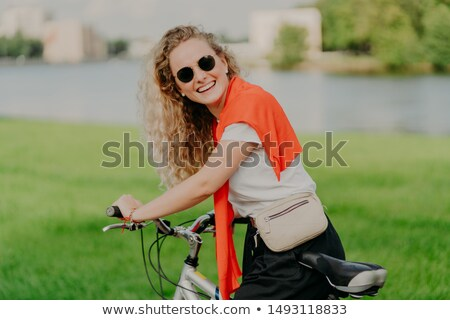 Outdoor shot of pleased active European woman with curly bushy hair, spends weekend riding bicycle,  Stock photo © vkstudio