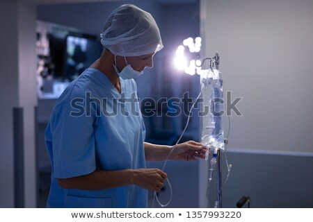 Side view of a Caucasian female surgeon checking intravenous therapy drip at hospital Stock photo © wavebreak_media
