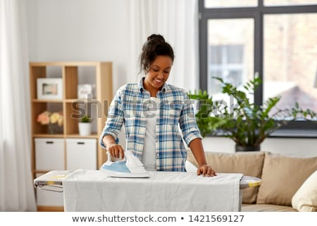 african american woman ironing bed linen at home Stock photo © dolgachov