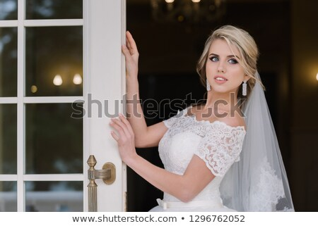 beautiful blonde woman in a pink dress at the opened white door stock photo © pilgrimego