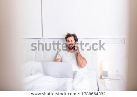 ハンサムな男 · ラップトップを使用して · ベッド · コンピュータ · 笑顔 · 男 - ストックフォト © wavebreak_media
