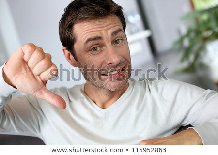 casual middle aged man sits with thumbs down  Stock photo © feedough