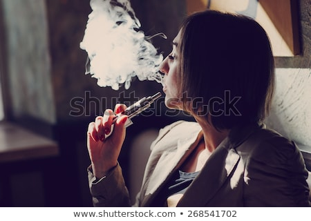 Woman smoking with electronic cigarette Stock photo © REDPIXEL