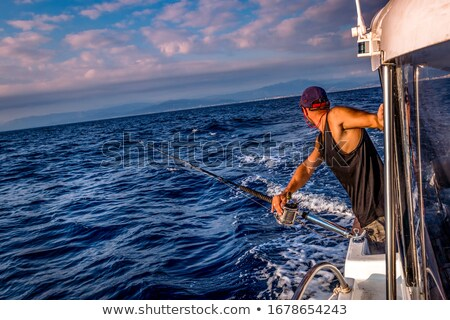 Young man fishing on a ocean Stock photo © dashapetrenko