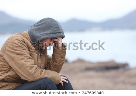 Depressive man in hooded jacket is crying  Stock photo © stevanovicigor