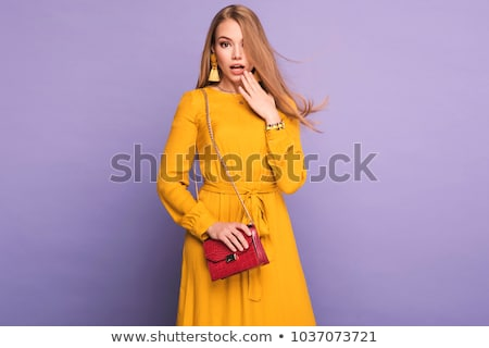 happy blond woman in yellow dress in studio stock photo © arturkurjan