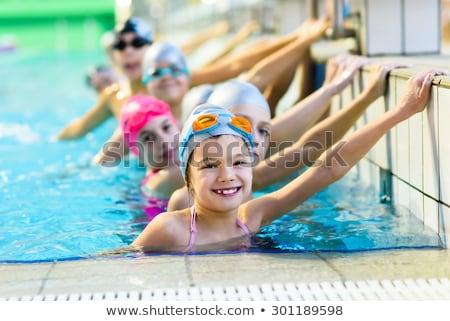 happy girl in blue goggles swimming in the swimming pool Stock photo © bubutu
