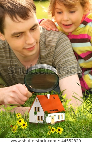 father with little girl looking on small house through magnifier stock photo © paha_l