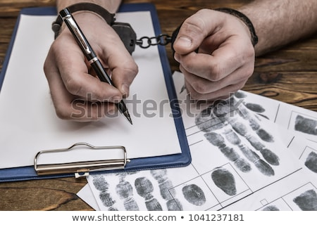 Male hands cuffed, top view of police investigator desk Stock photo © stevanovicigor