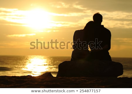 back view of couple sitting and relaxing on the beach stock photo © deandrobot