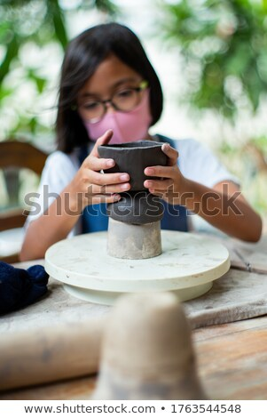 Stock photo: Attentive girl molding a clay