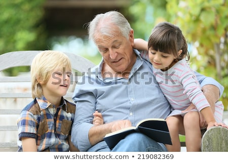 senior man reading book to boy Stock photo © IS2