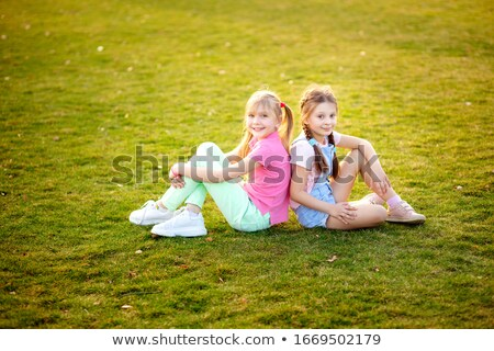 Young girl sitting on grass laughing Stock photo © IS2
