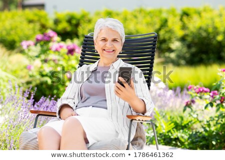 woman sitting in chair outdoors stock photo © is2