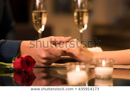 Holding hands at the dinner table Stock photo © IS2