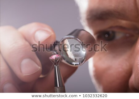 person looking at diamond with magnifying loupe stock photo © andreypopov
