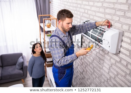 Técnico examinar acondicionador de aire digital mirando Foto stock © AndreyPopov