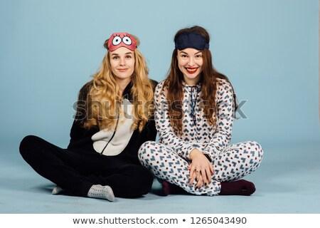 two women in pajamas sit on floor on a blue background studio shoot stock photo © ruslanshramko