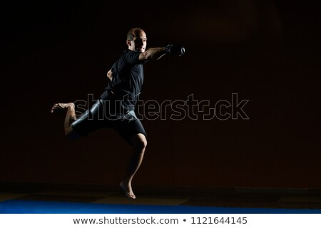 Athlete jumping over blue tatami beats with a hand Stock photo © Andreyfire