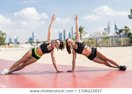 couple doing side plank exercise on summer beach stock photo © dolgachov
