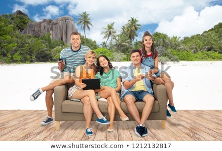 friends with tablet pc and smartphones over beach Stock photo © dolgachov