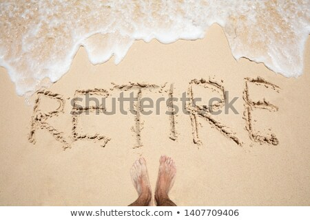 Man's Foot Near The Word Retire On Sand Stock photo © AndreyPopov