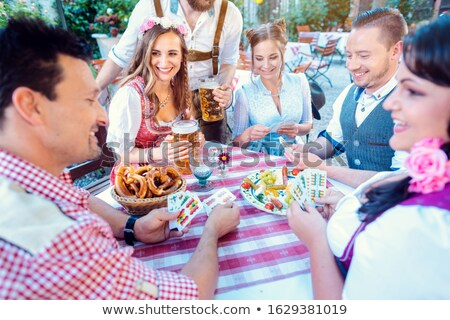 Friends in Bavarian beer garden playing traditional card game Stock photo © Kzenon