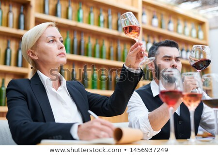 Female sommelier and her colleague in formalwear looking at wine in bokals Stock photo © pressmaster