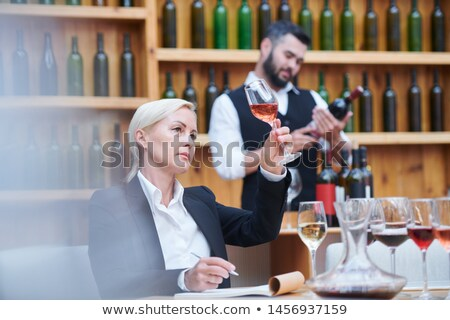 Blonde female sommelier examining sample of wine or brandy in bokal Stock photo © pressmaster