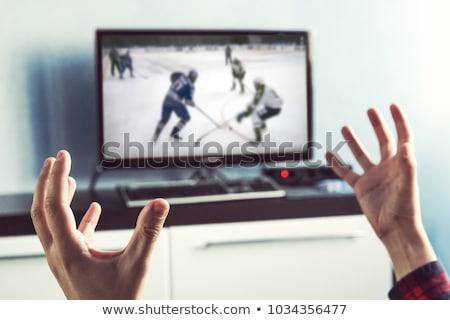 Człowiek oglądania hokej gry telewizja domu Zdjęcia stock © dolgachov