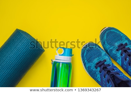 Everything for sports turquoise, blue shades on a yellow background. Yoga mat, sport shoes sportswea Stock photo © galitskaya