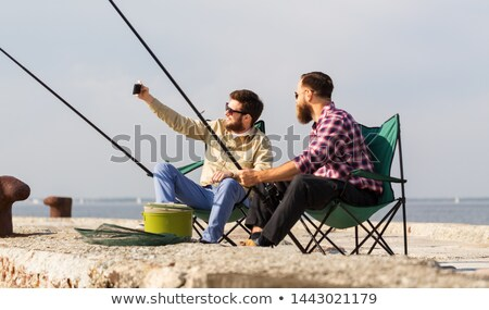 friends fishing and taking selfie by smartphone Stock photo © dolgachov