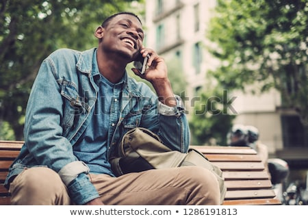 cheerful man sits on a bench in the city and talks on the phone stock photo © ruslanshramko