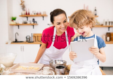 Adorable joyful child with touchpad showing his mom video recipe Stock photo © pressmaster