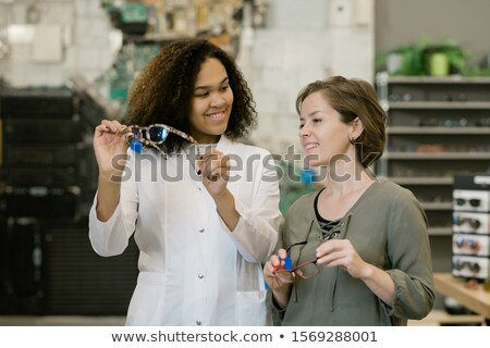 Happy young client of optics shop looking at eyeglasses held by clinician Stock photo © pressmaster