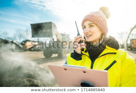 Manager in biomass and landfill operation using her radio in front of machines Stock photo © Kzenon