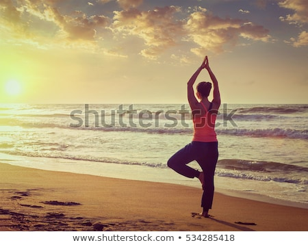 Young sporty fit woman doing yoga at beach on sunset Stock photo © dmitry_rukhlenko