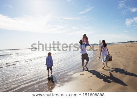 rear view of family walking along beach with picnic basket stock photo © monkey_business