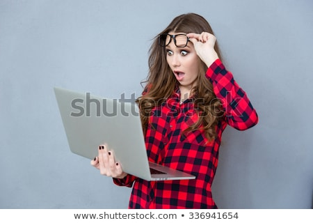 Portrait of shocked girl with opened mouth using laptop Stock photo © deandrobot