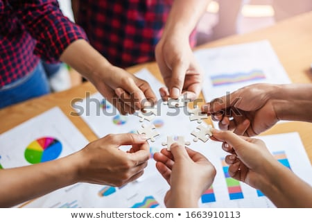 Synergy against business colleagues holding piece of puzzle Stock photo © wavebreak_media